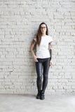Детеныши татуировали женщину нося пустую футболку, стоя перед кирпичной стеной в просторной квартире стоковое фото rf