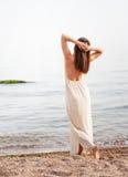 Детеныши уменьшают женщину одетую в длинном белом платье с открытым назад, расслабленное положение назад стоковая фотография rf