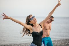 Детеныши уменьшают красивую женщину на пляже, шаловливый, танцуя, летних каникулах, имеющ потеху, положительное настроение, счаст стоковое изображение rf