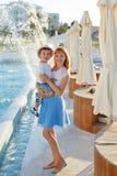 Детеныши уменьшают мать в голубой юбке держа ее руки и laug сына стоковое изображение