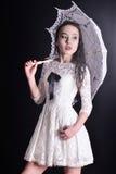 Детеныши уменьшают модель в светлом платье лета при филигранный зонтик представляя в студии Черная предпосылка Стоковое Фото