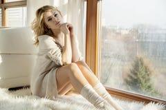 Детеныши уменьшают сексуальную женщину в коричневом свитере против окна стоковое фото