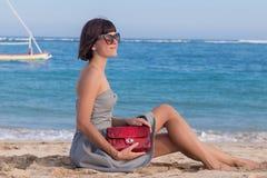 Детеныши уменьшают сексуальную женщину на пляже Роскошное handmade snakeskin в ее руках Стоковое Изображение
