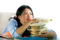Детеныши усилили и расстроили азиатского китайского студента подростка работая крепко полагаться на куче блокнотов и книг на сокр стоковая фотография rf