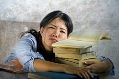 Детеныши усилили и расстроили азиатского корейского студента подростка работая крепко полагаться на куче блокнотов и книг на сокр стоковые изображения rf