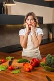 Детеныши удивили женщину домохозяйки варя в кухне Стоковое Изображение RF