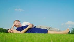 Детеныши экономно расходуют при его беременная жена ослабляя в парке, совместно лежат на зеленой траве акции видеоматериалы