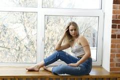 Детеныш девушки сидит на windowsill Стоковое фото RF