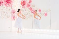 Детеныш и неимоверно красивая балерина представляющ и танцующ в белой студии вполне света Стоковое Изображение RF