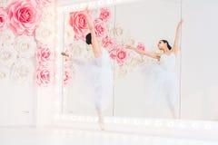 Детеныш и неимоверно красивая балерина представляющ и танцующ в белой студии вполне света Стоковое Изображение