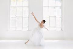 Детеныш и неимоверно красивая балерина представляющ и танцующ в белой студии Стоковое Изображение