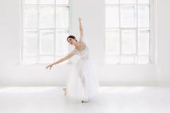 Детеныш и неимоверно красивая балерина представляющ и танцующ в белой студии Стоковые Изображения RF