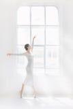 Детеныш и неимоверно красивая балерина представляющ и танцующ в белой студии Стоковые Изображения