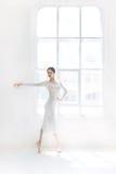 Детеныш и неимоверно красивая балерина представляющ и танцующ в белой студии Стоковое фото RF