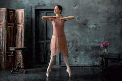 Детеныш и неимоверно красивая балерина представляющ и танцующ в черной студии Стоковая Фотография