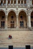 Детеныш обнимая пар держит руки и сидит на лестницах старого исторического здания в Будапеште, Венгрии Стоковое Изображение RF