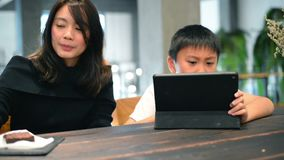 Дети азиатской матери уча как использовать цифровой планшет видеоматериал