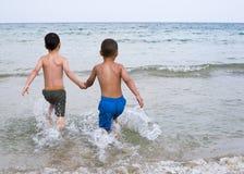 Дети бежать в море Стоковое фото RF