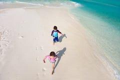 Дети бежать на пляже стоковые изображения rf