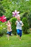Дети бежать с ветрянками в саде Стоковое фото RF