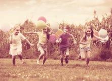 Дети бежать с воздушными шарами в парке Стоковое фото RF