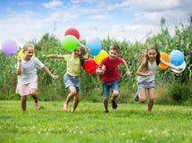 Дети бежать с воздушными шарами в парке Стоковое Изображение RF