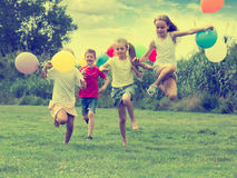 Дети бежать с воздушными шарами в парке Стоковое Фото