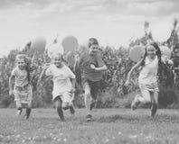 Дети бежать с воздушными шарами в парке Стоковая Фотография