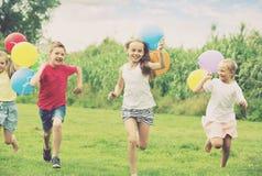 Дети бежать с воздушными шарами в парке Стоковая Фотография RF
