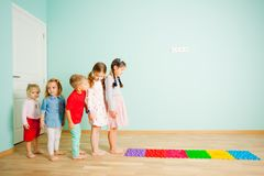 Дети босоногие стоят в ряд между циновками массажа стоковые фотографии rf