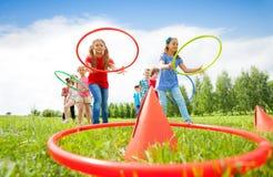 Дети бросают красочные обручи на конусах пока состязающся Стоковые Фотографии RF