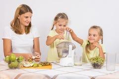 Дети бросают плодоовощ в juicer в заботе матерей Стоковые Фотографии RF