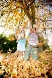 Дети бросая листья в парке Стоковые Изображения