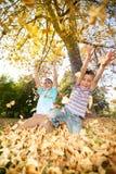Дети бросая листья в парке Стоковые Фото