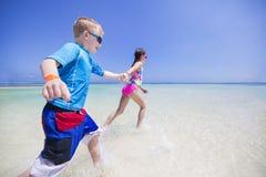 Дети брызгая в океане на тропическом пляже отдыхают Стоковое Изображение