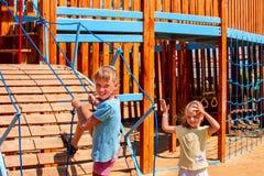 Дети двигают вне к скольжению в спортивной площадке Стоковые Фото