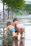 Дети вползая в лужице на парке Стоковая Фотография