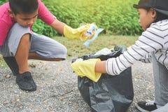 Дети вручают в желтых перчатках выбирая вверх пустую пластмассы бутылки в сумку ящика Стоковое Изображение