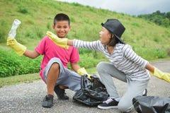 Дети вручают в желтых перчатках выбирая вверх пустую пластмассы бутылки в сумку ящика Стоковые Фото