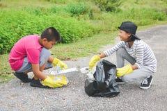 Дети вручают в желтых перчатках выбирая вверх пустую пластмассы бутылки в сумку ящика Стоковая Фотография