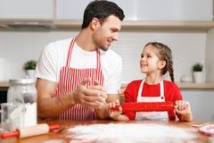 Дети, выпечка, концепция семьи Жизнерадостный мужчина брюнет носит рисберму и замешивает тесто, счастливая девушка держит вращающ Стоковая Фотография RF
