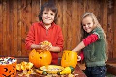 Дети высекая их Джек-o-фонарики тыквы Стоковая Фотография RF