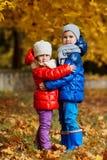 Дети в желтом парке осени Мальчики и положение девушки Стоковые Изображения