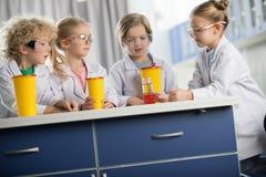 Дети в защитных стеклах делая эксперимент стоковая фотография