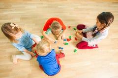 Дети в здании детского сада от деревянных кирпичей стоковые изображения