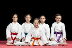 Дети в кимоно сидя на tatami на семинаре боевых искусств Селективный фокус стоковые изображения