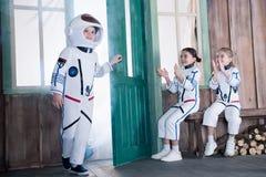 Дети в костюмах астронавта, девушки аплодируя к мальчику Стоковые Изображения