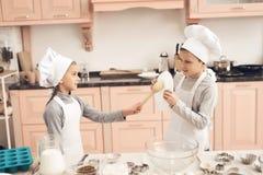 Дети в кухне Брат и сестра воюют с ложками Стоковые Изображения