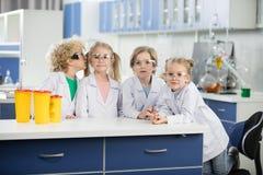 Дети в пальто лаборатории науки нося и положение на таблице Стоковые Фотографии RF