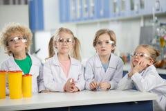 Дети в пальто лаборатории науки нося и положение на таблице Стоковая Фотография